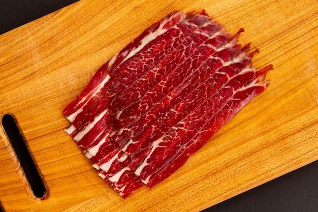 Bacon séché juteux parfumé avec des épices sur la planche à découper en acacia. vue de dessus. lay plat.