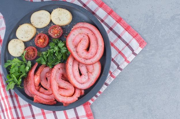 Bacons grillés aux légumes sur une poêle à frire.