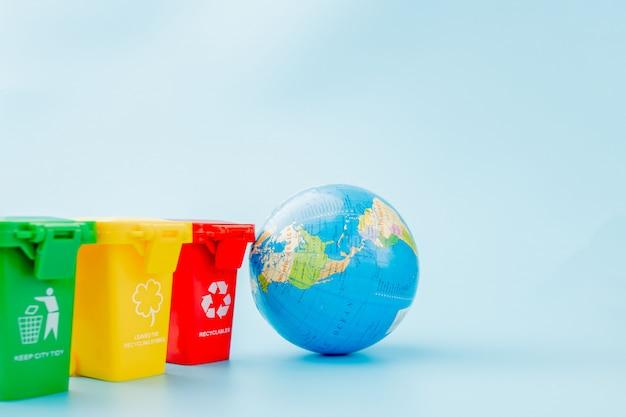 Bacs de recyclage jaune, vert et rouge avec symbole de recyclage sur fond bleu.