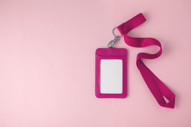 Badge en cuir et lanière sur fond rose