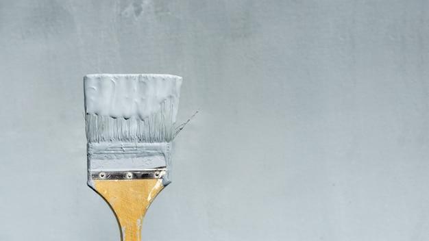 Badigeonner de peinture sur le fond d'un mur de réparation bleu.