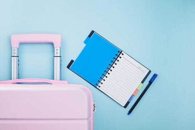 Bagage rose avec un journal de la liste de contrôle sur le bleu pour le concept de planification de voyage