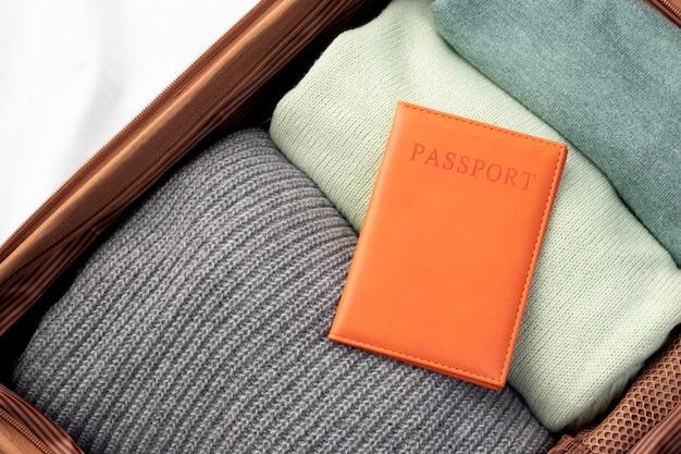 Bagages ouverts avec vêtements pliés et passeport