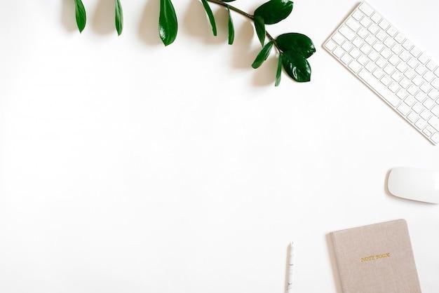 Bagages plats, bureau de bureau vue de dessus. un lieu de travail avec des verrous verts, un clavier et une souris sans fil, un ordinateur portable et un stylo. copier l'espace