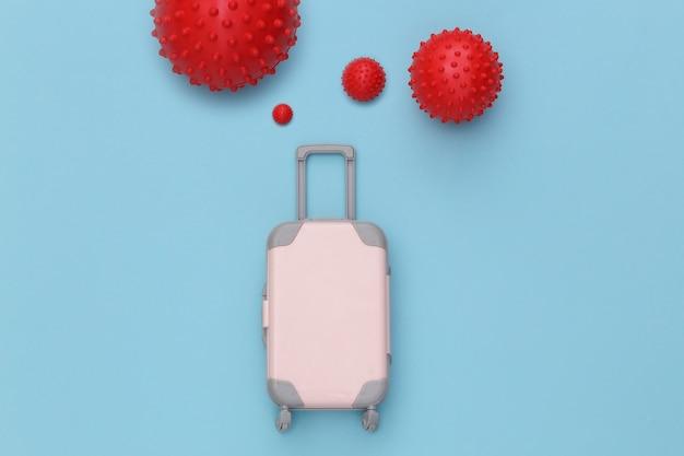 Bagages de voyage et molécules de souche virale sur fond bleu. voyager pendant la pandémie de covid-19.