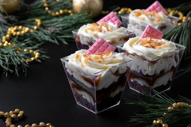Bagatelles à base de biscuit au chocolat fourré au caramel et aux cacahuètes. le dessert est décoré de crème de fromage crémeuse et de chocolat rose. fermer