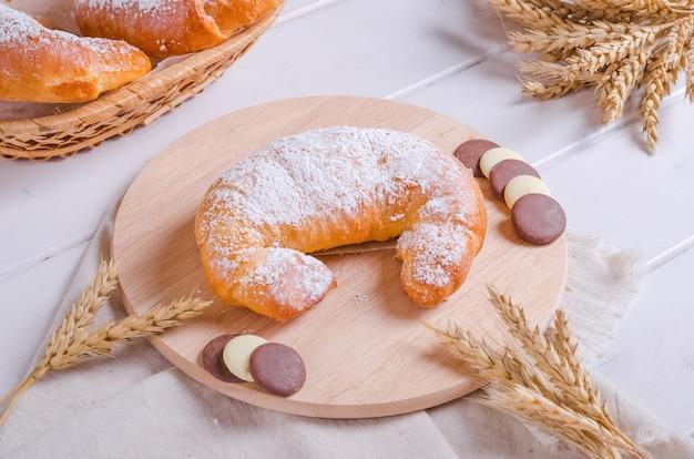 Bagel frais et savoureux fourré au chocolat sur une planche de bois ronde sur fond de bois blanc