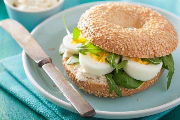 Bagel de petit déjeuner avec œuf, fromage à la crème et roquette