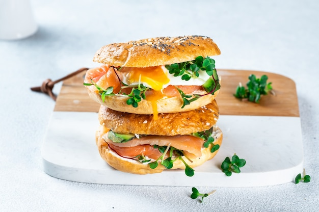 Bagel sain fraîchement cuit au four rempli de saumon, microgreen, avocat et œuf. servi sur un bureau blanc. sandwich au saumon. petit-déjeuner sain.