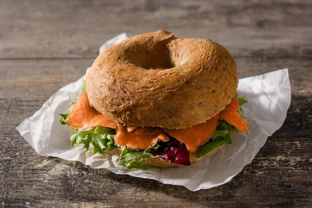 Bagel sandwich au fromage à la crème, saumon fumé et légumes sur une table en bois