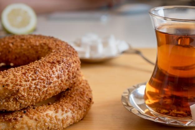 Bagel traditionnel turc croustillant / simit au sésame et verre de thé noir turc, concept de pâtisserie de petit-déjeuner turc