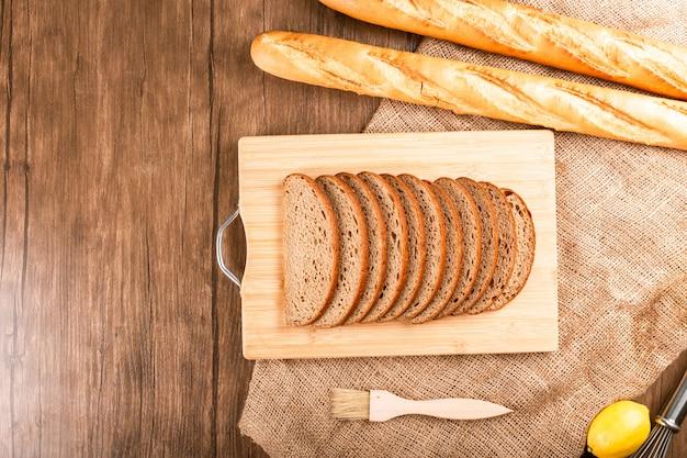 Bagel et tranches de pain noir sur planche de cuisine