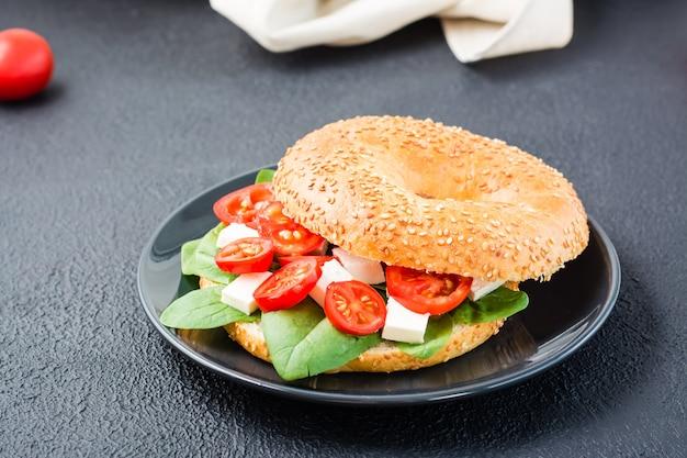 Des bagels appétissants prêts à manger farcis de tomates, de feta et de feuilles d'épinards sur une assiette sur fond noir. collation légère et saine