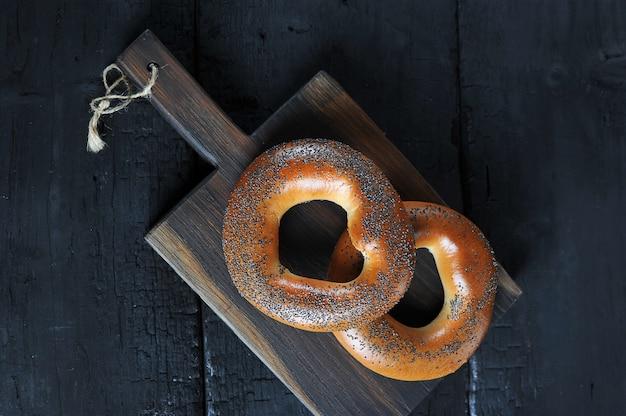 Bagels aux graines de pavot sur une planche de bois