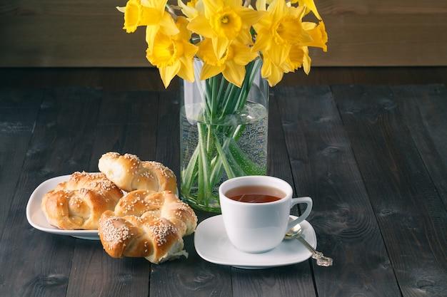 Bagels croustillants au sésame fraîchement cuits au four avec une tasse de thé