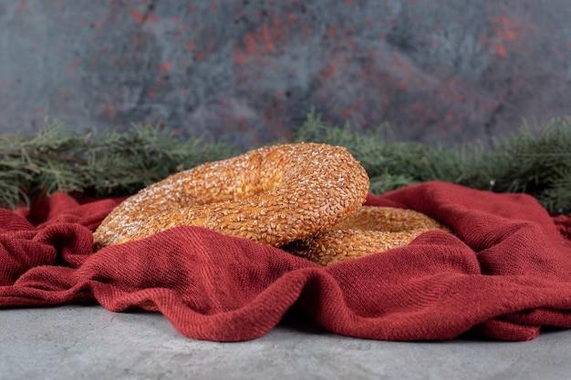 Des bagels croustillants enrobés de sésame assis dans un arrangement décoratif sur une surface en marbre