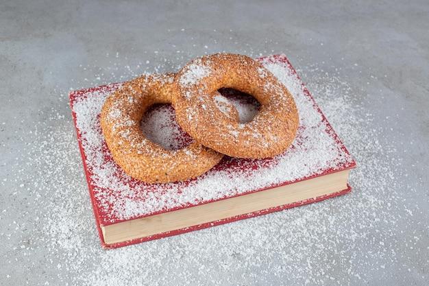 Bagels enrobés de sésame croustillant sur un plateau recouvert de poudre de noix de coco sur une surface en marbreq