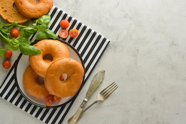 Bagels isolés sur un tableau lumineux au basilic et tomates cerises pour le petit déjeuner. pâtisserie.