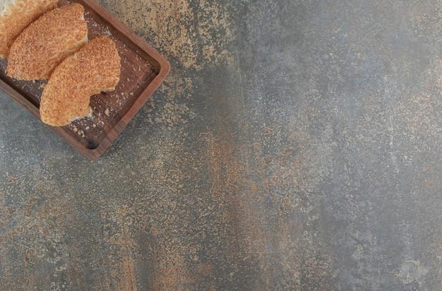 Bagels en tranches regroupés sur une planche de bois sur une serviette,