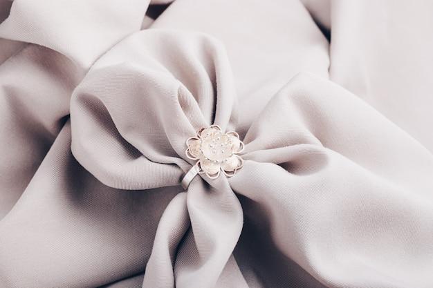 Bague en argent en forme de fleur sur un tissu beige