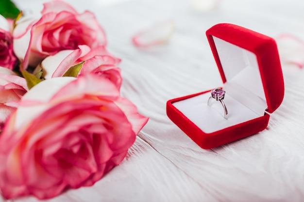 Bague en argent avec gemme d'améthyste dans une boîte cadeau rouge et bouquet de roses