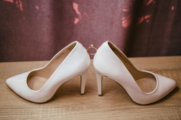 Bague diamant or entre paire de chaussures à talons hauts blancs