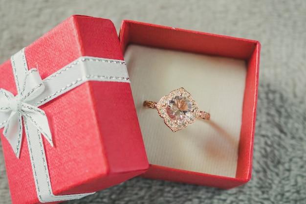 Bague diamant rose dans une boîte cadeau rouge