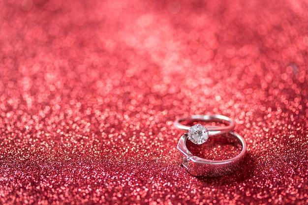 Bague en diamant sur la texture de paillettes rouges
