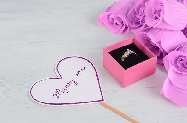 Bague à diamants dorés dans une boîte rose avec bouquet de roses roses