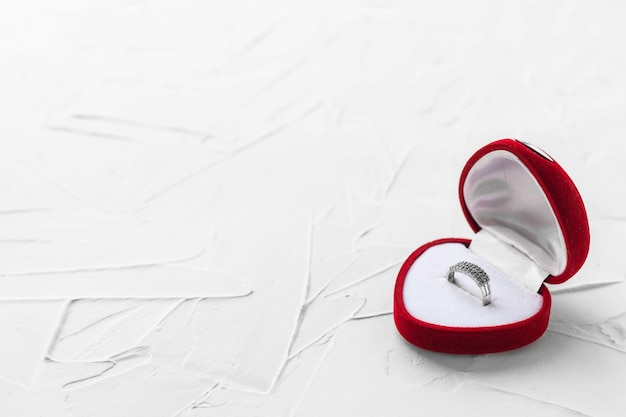 Bague de fiançailles en argent dans une boîte en velours rouge en forme de cœur. accessoire avec des pierres précieuses. cadeau romantique