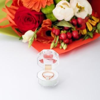 Bague de fiançailles dans une boîte cadeau avec bouquet de fleurs aux couleurs vives. l'offre de se marier. cadeau pour la saint-valentin. proposition de mariage pour femme bien-aimée. symbole d'amour et de mariage.