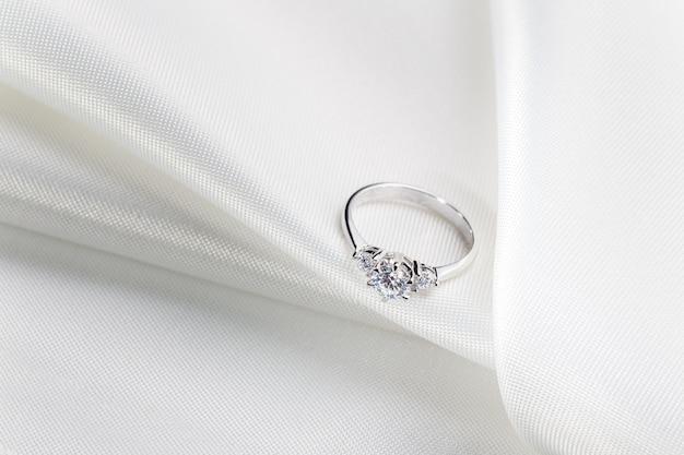 Bague de fiançailles en diamant sur tissu blanc