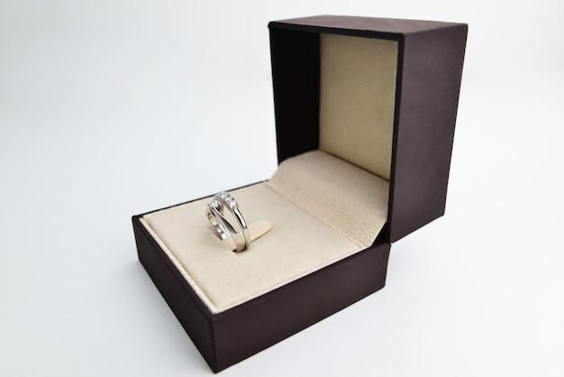 Bague de fiançailles en or blanc et diamants dans un écrin noir et blanc