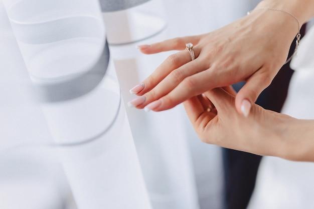 Bague de fiançailles avec une pierre sur la main de la douce épouse