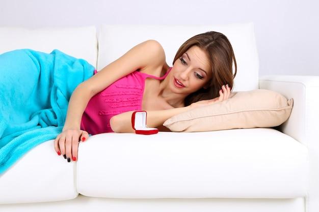 Bague de mariage dans jolie boîte sur canapé près de fille endormie, gros plan