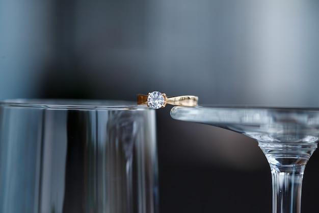 Une bague de mariage en métal précieux avec une pierre en diamant se trouve dans un verre
