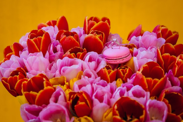 Bague de mariage se dresse sur un macaron rose sur un bouquet de tulipes
