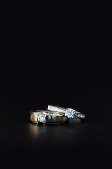 Bague de mariage sur table noire avec un flou artistique et plus de lumière en arrière plan