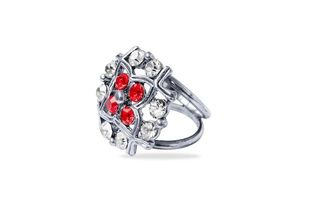 Bague en métal blanc avec pierres rouges et transparentes, gros plan, isolé sur fond blanc