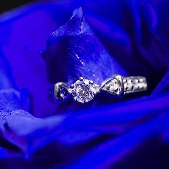 Bague en or blanc et diamants dans des pétales de roses bleues