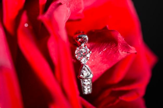 Bague en or blanc et diamants dans des pétales de roses rouges