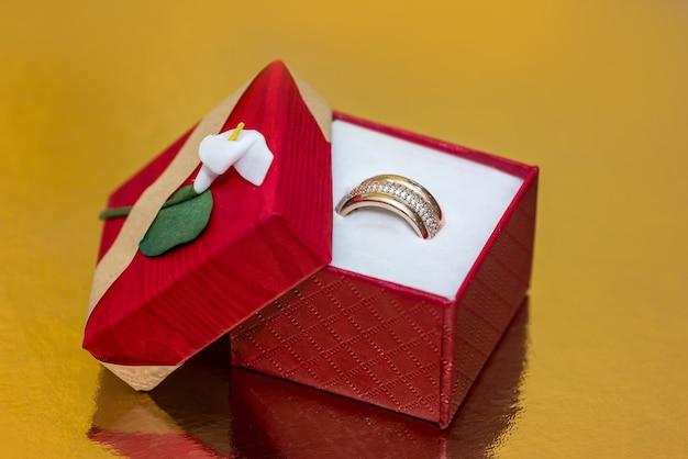 Bague en or dans une boîte cadeau rouge sur une surface dorée