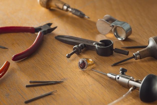 Bague en or de luxe avec pierre précieuse rubis sur l'établi du bijoutier. lieu de travail d'un bijoutier. outils et équipement pour le travail des bijoux sur un bureau en bois antique.