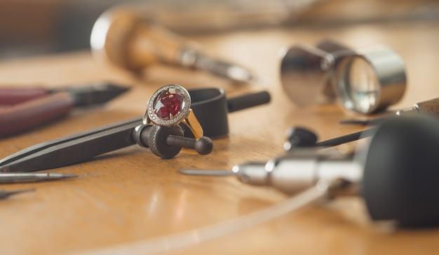 Bague en or de luxe avec pierre précieuse rubis sur l'établi du bijoutier.