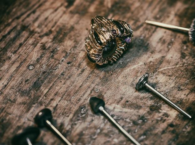 Bague en or avec pierres précieuses et divers outils de bijouterie sur une vieille surface en bois.