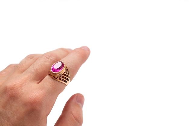 Une bague en or avec un rubis au doigt de la main