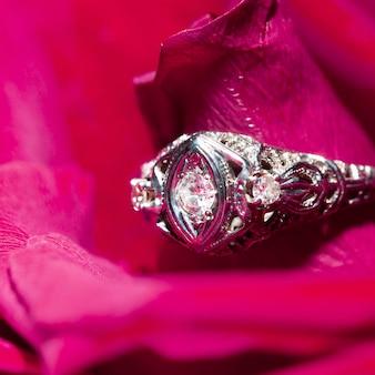 Bague en platine avec un diamant sur une rose rouge, close-up