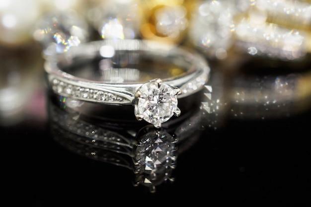 Bagues en diamant de bijoux de luxe avec réflexion sur fond noir