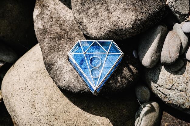 Les bagues de fiançailles en argent doré de mariage se trouvent dans une boîte en métal en forme de verre en forme de diamant