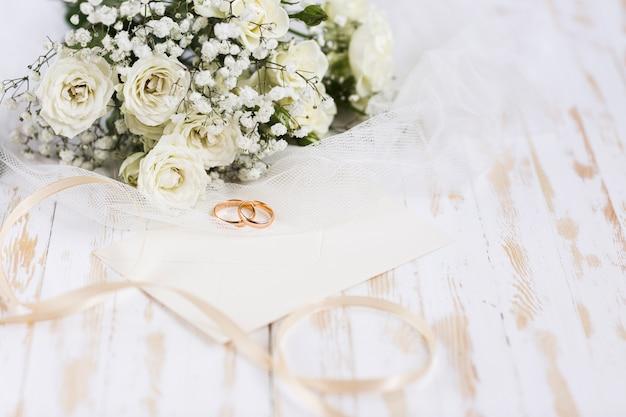 Bagues de fiançailles grand angle à côté des fleurs
